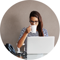Young woman sips on a mug while working on a laptop.