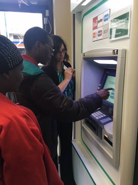 Woman helps a man and woman use an ATM.