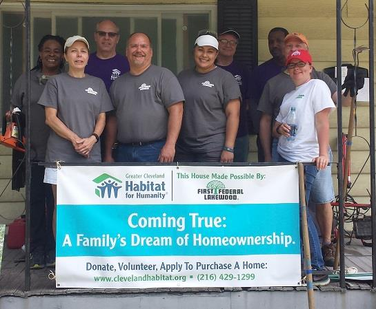 Group of Habitat for Humanity workers pose on a porch with a Habitat for Humanity sign.