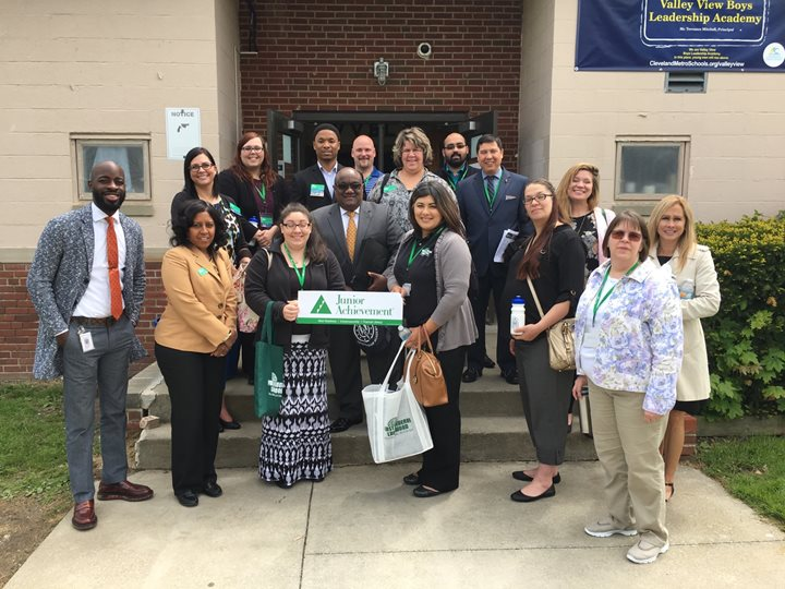 First Federal employees pose in front of a school with a Junior Achievement sign.